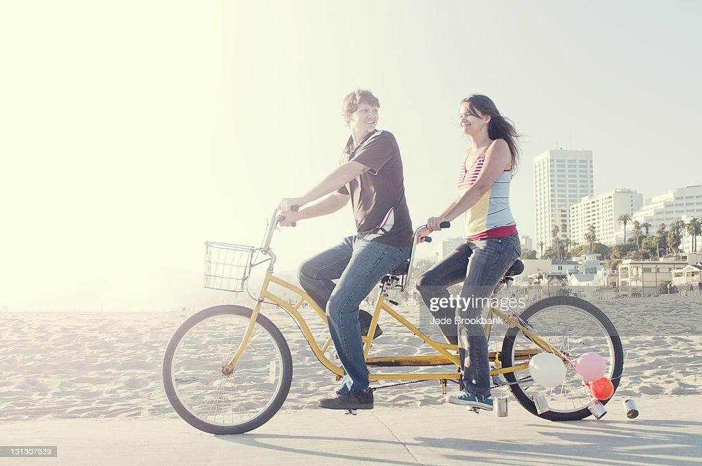 Couple riding tandem bike on beach boardwalk