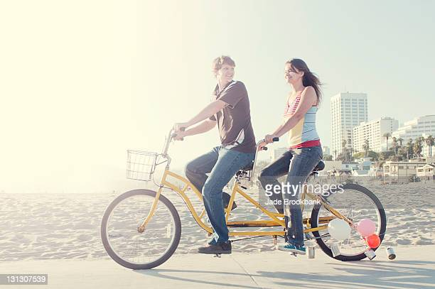Couple riding tandem bike on beach boardwalk