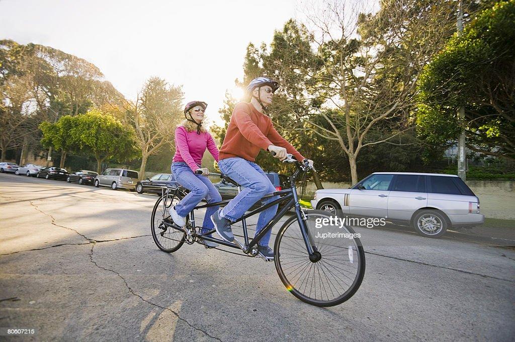 Couple riding tandem bike