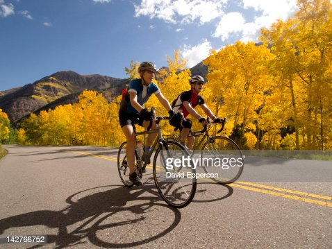 Couple road cycling in fall colors : Stock Photo