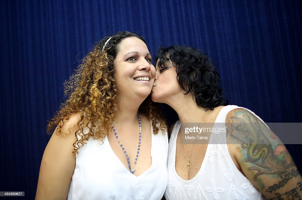 Couple Roberta Felitte and Karina Soares, together five years, kiss while posing before marrying at what was billed as the world's largest communal gay wedding on December 8, 2013 in Rio de Janeiro, Brazil. 130 couples were married at the event which was held at the Court of Justice in downtown Rio. In May, Brazil became the third country in Latin America to effectively approve same-sex marriage via a court ruling, but a final law has yet to be passed.