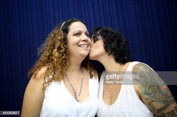 Couple Roberta Felitte and Karina Soares together five years kiss while posing before marrying at what was billed as the world's largest communal gay...