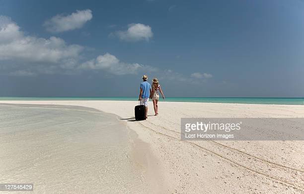 Couple rolling luggage on beach