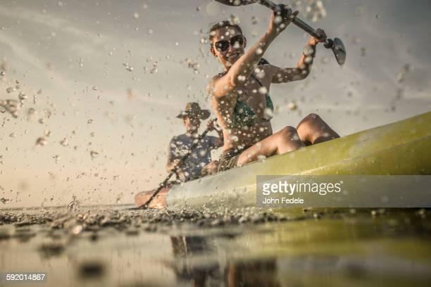 Couple rowing canoe on still lake