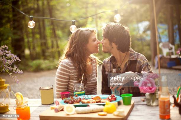 Couple rubbing noses at picnic table in forest