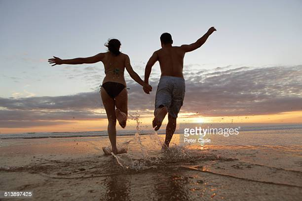 Couple runng into sea at sunset