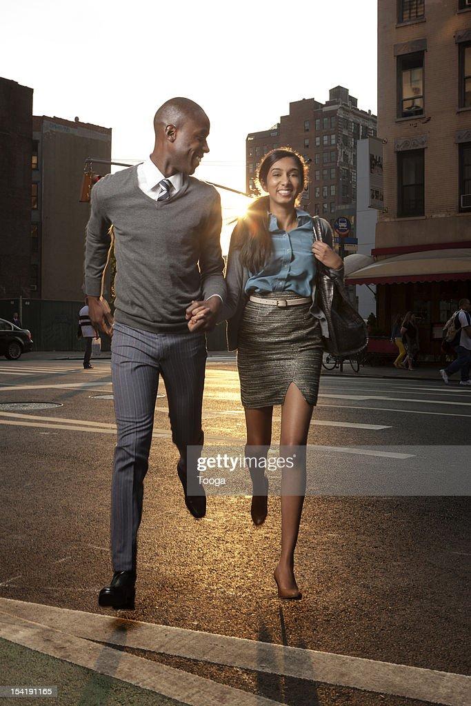 Couple running across street smiling : Stock Photo