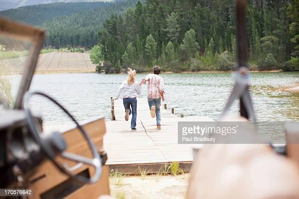 Couple jogging le long de la jetée du lac