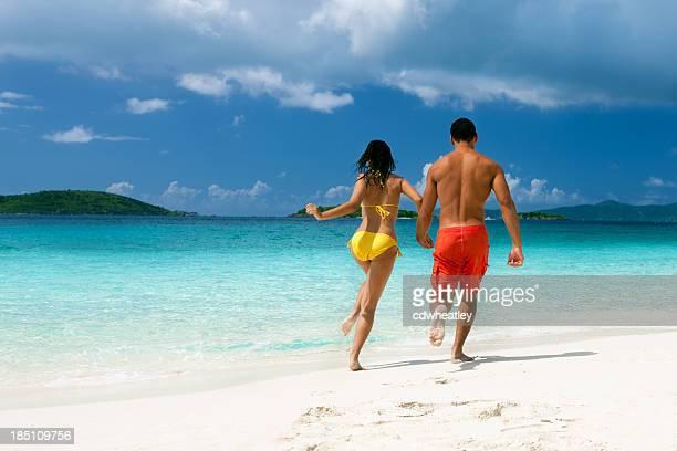 couple running along the Caribbean beach shoreline