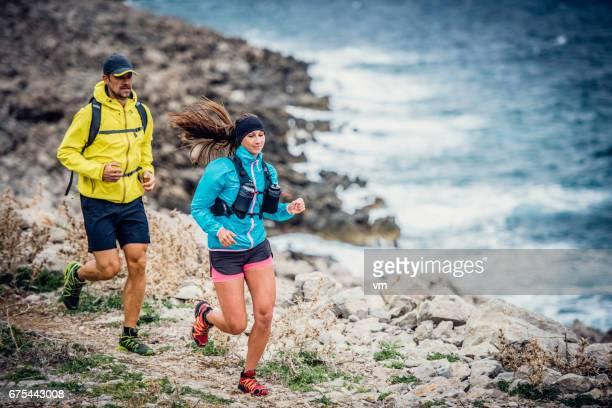 Couple running along the shoreline
