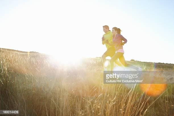 Couple running in grassy field