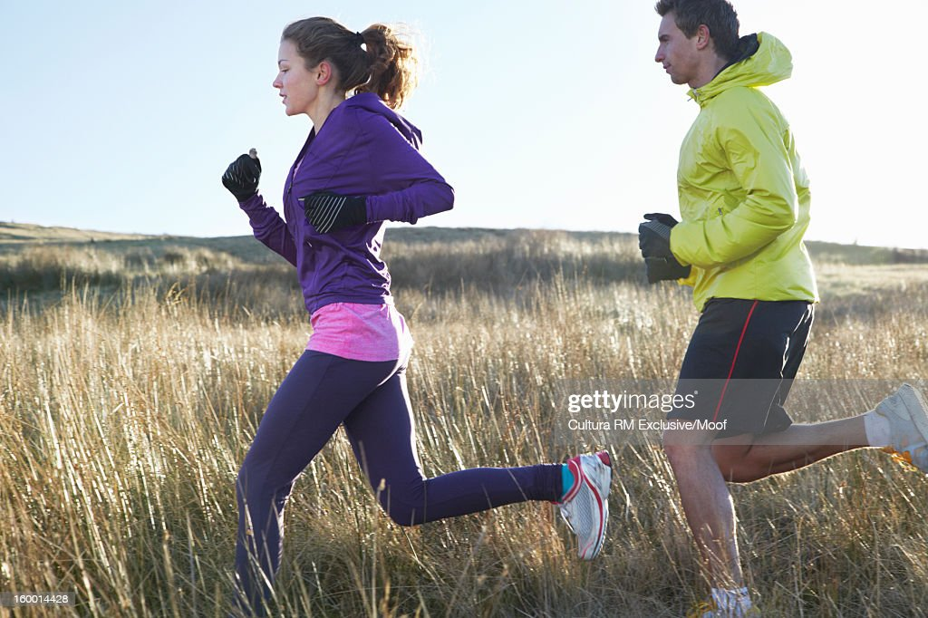 Couple running in grassy field