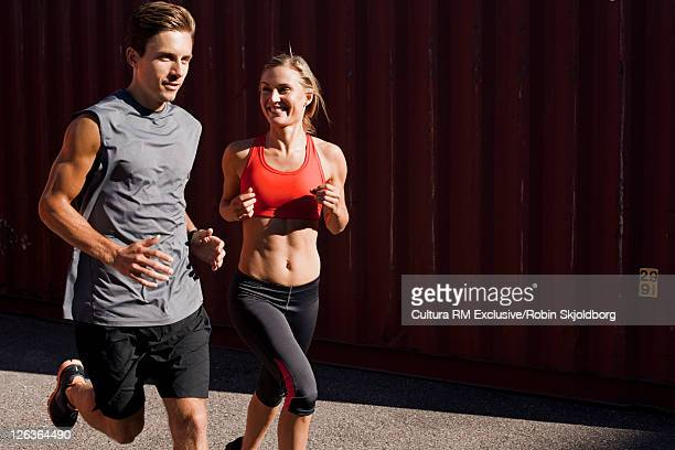 Couple running in industrial area