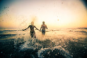 Silhouette of couple in love running in the ocean and holding hands.