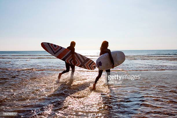 Couple running in water carrying surfboards.