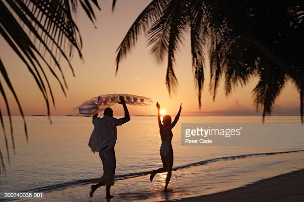 Couple running on beach, man holding inflatable raft, at sunset