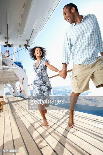 Couple Running On Cruise Ship Deck Stock Photo