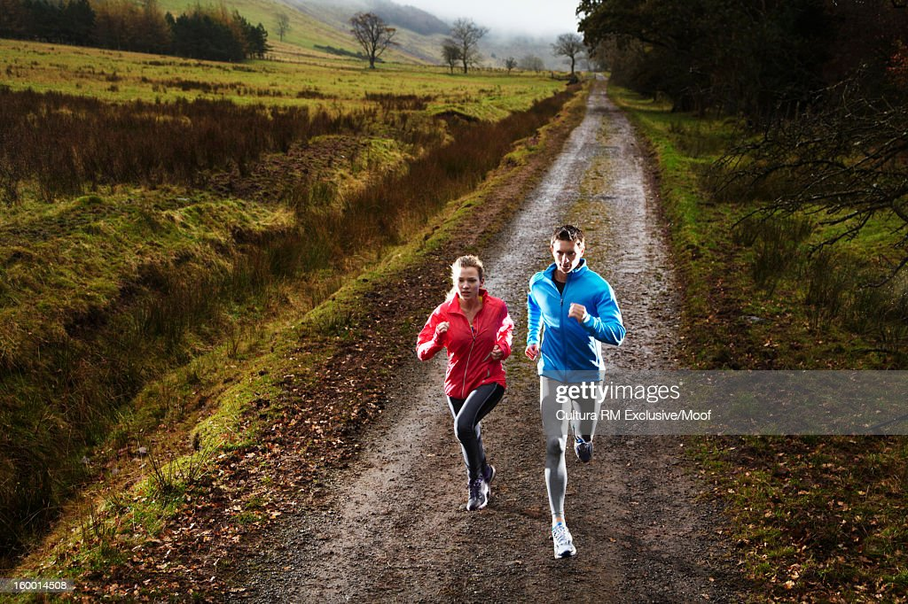 Couple running on dirt road : Stock Photo