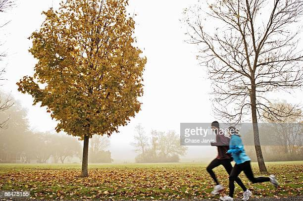 Couple running on foggy autumn morning