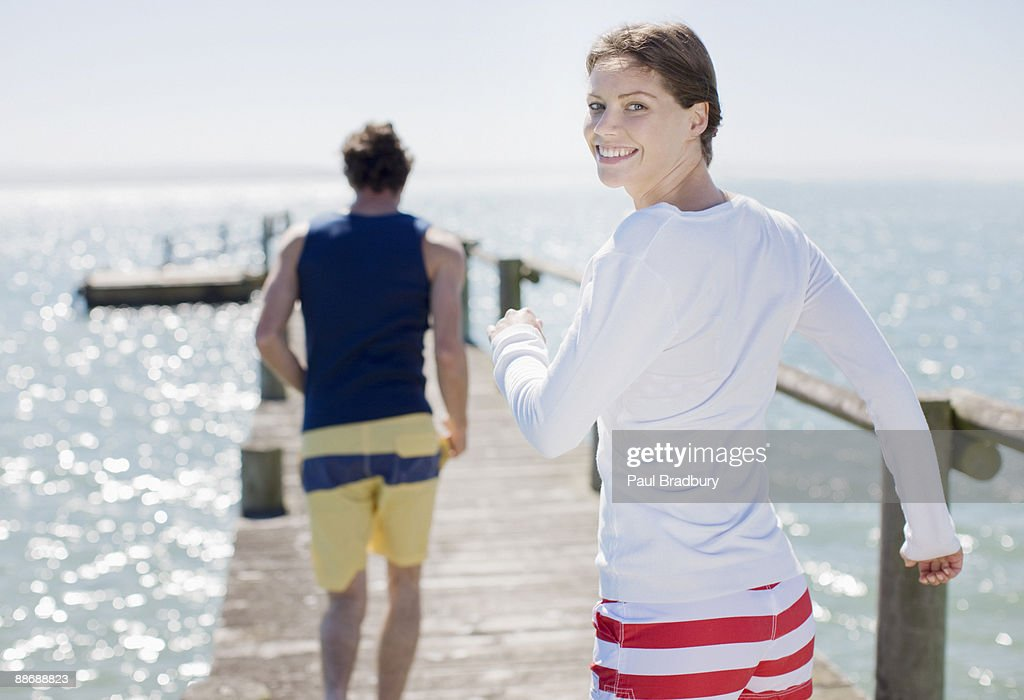 Couple running on pier by ocean