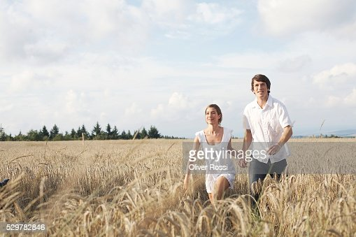 Couple Running Through Field : Stock-Foto