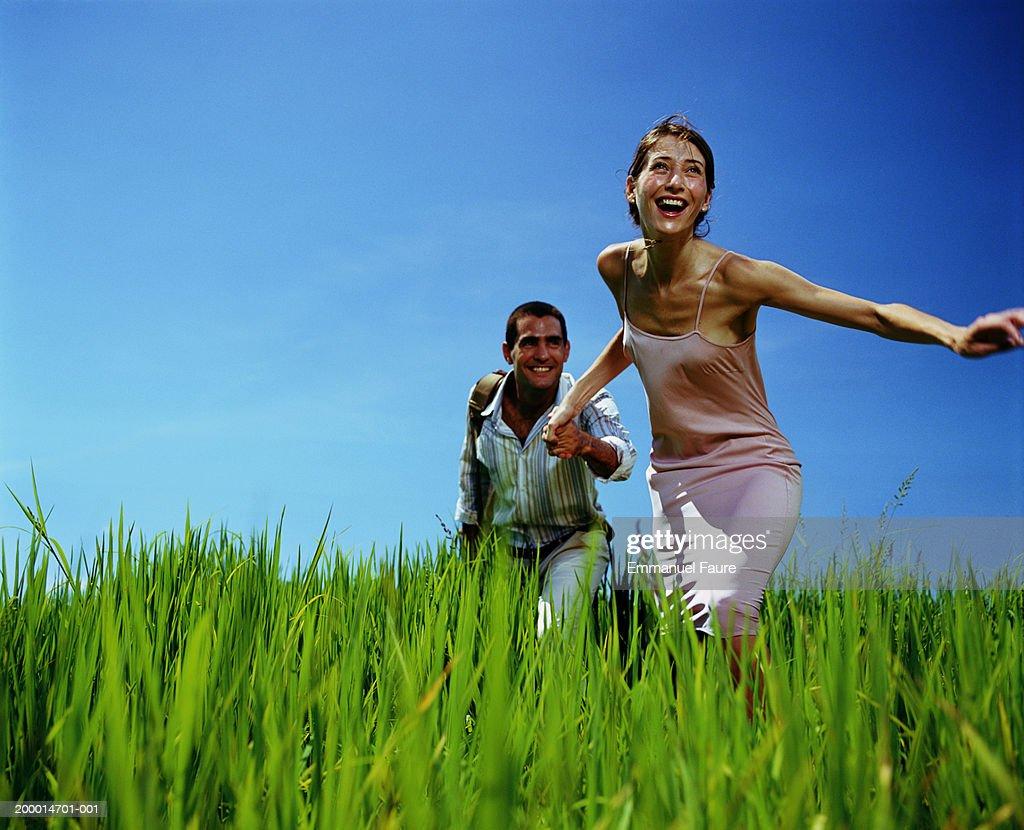 Couple running through rice field : Stock Photo