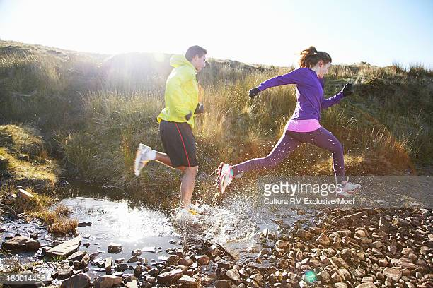 Couple running through rocky creek