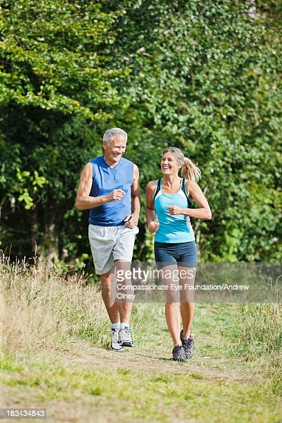 Couple running together in woods