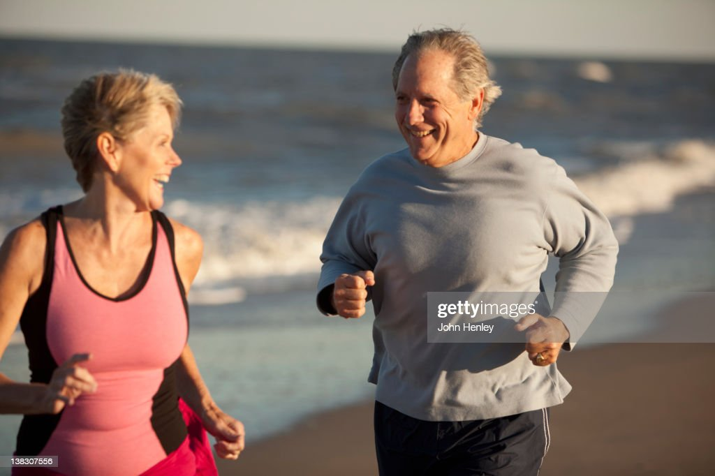 Couple running together on beach : Stock Photo