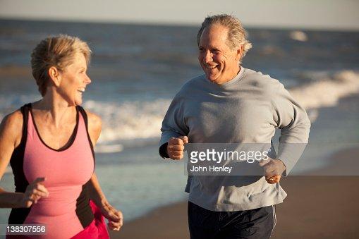 Couple running together on beach : Bildbanksbilder
