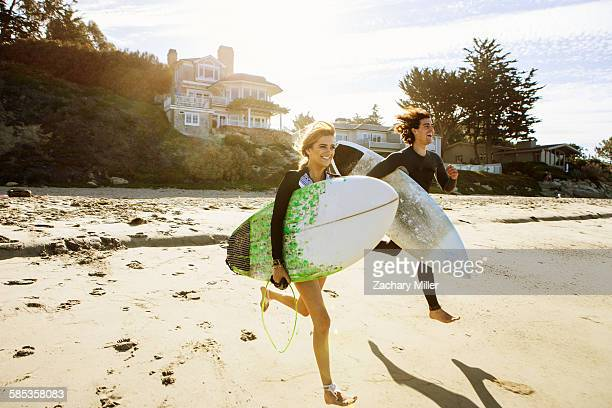 Couple running towards sea, carrying surfboards