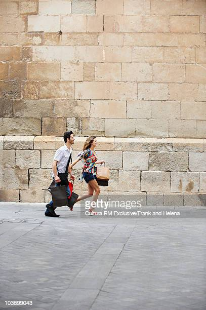 Couple running with shopping bags