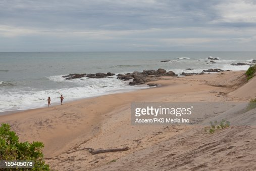 Couple runs into surf from empty beach : Stock Photo