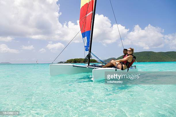 couple sailing a catamaran in the Caribbean
