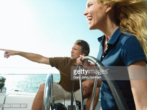 Couple sailing on yacht, woman steering, man directing, side view : Stock Photo