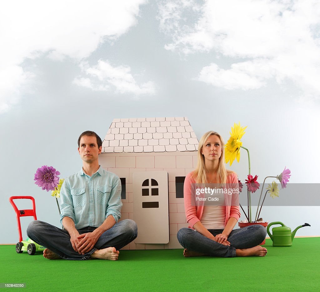 Couple sat in front of cardboard house : Stock Photo