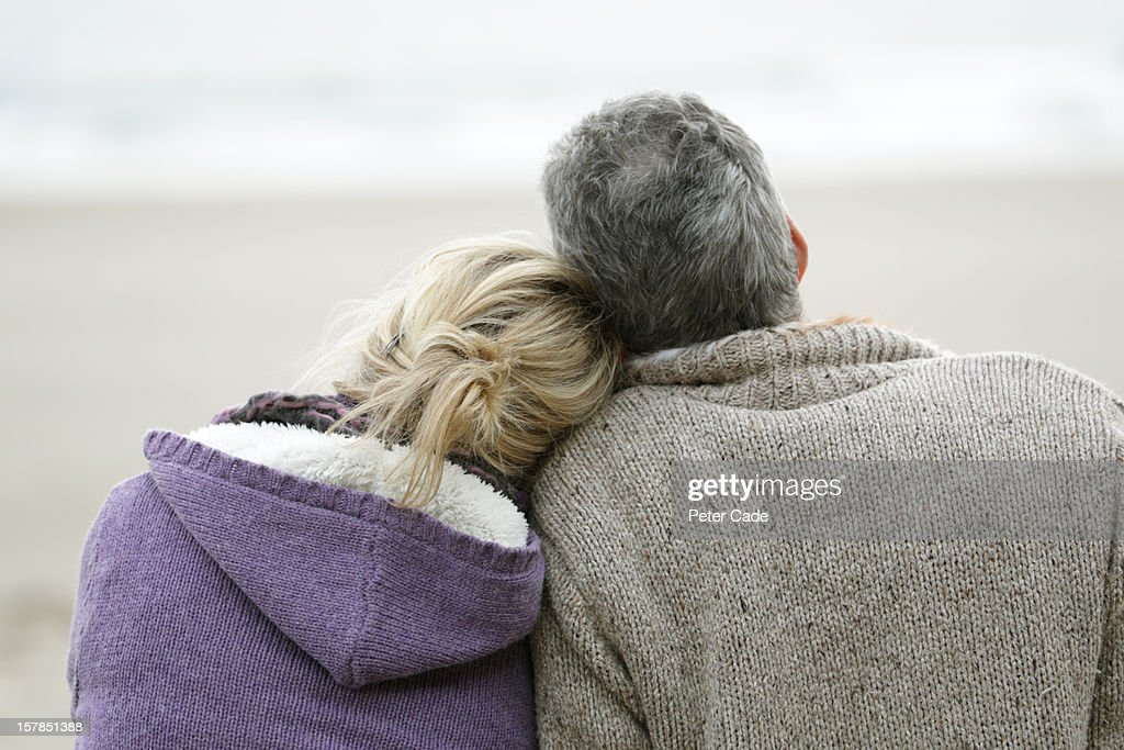 Couple sat on beach in winter looking out to sea