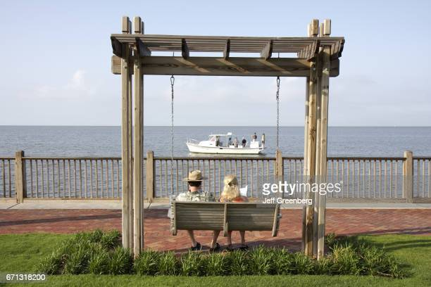 A couple sat on the love seat swing at the Grand Hotel Marriott Resort