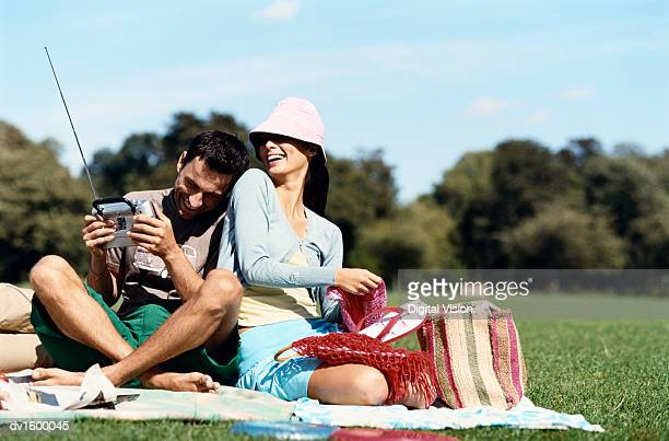 A Couple Sat Together on a Blanket in a Park, the Man Holding a Portable Radio, the Woman Wearing a Sunhat