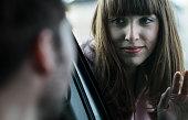 Couple saying farewell through windscreen