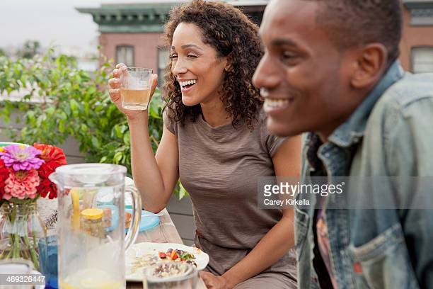Couple seated at a picnic table at a roof party