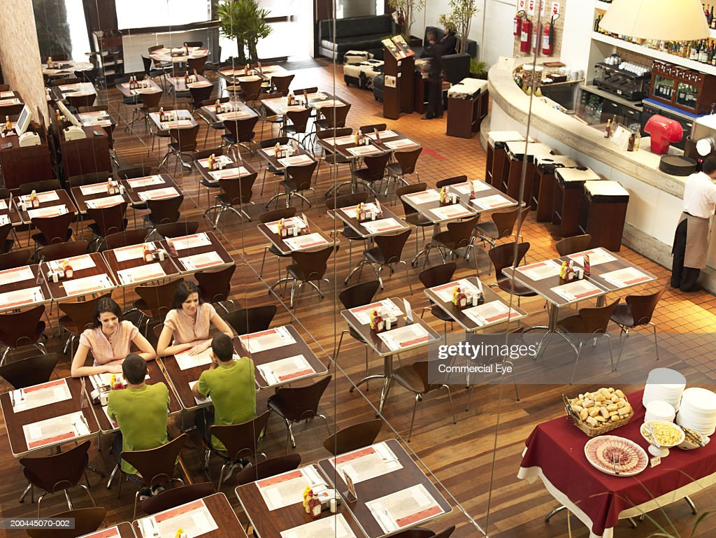 Couple seated in cafeteria, elevated view, reflection in mirror : Stock Photo