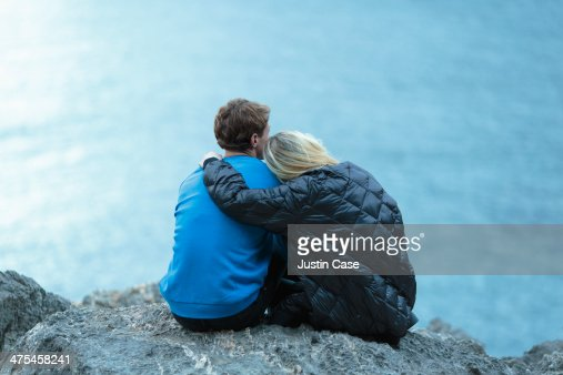 couple seating together facing the blue sea : Stock Photo