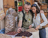 Couple selecting spices from sacks at front of shop