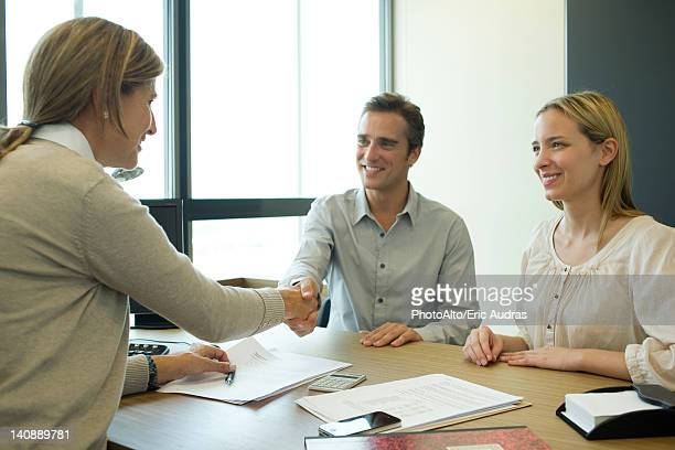 Couple shaking hands with businesswoman in office