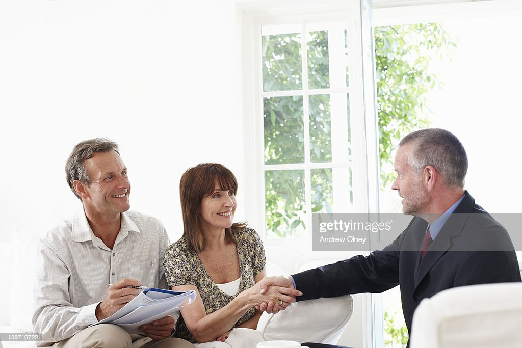 Couple shaking hands with financial advisor : Stock Photo
