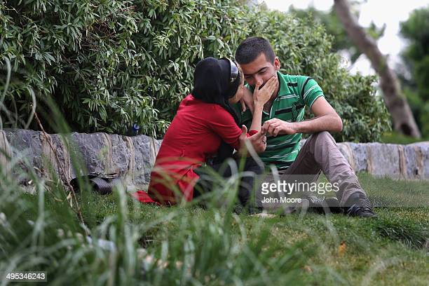 A couple share a moment together behind a park hedgerow on June 2 2014 in Isfahan Iran Isfahan with it's immense mosques picturesque bridges and...