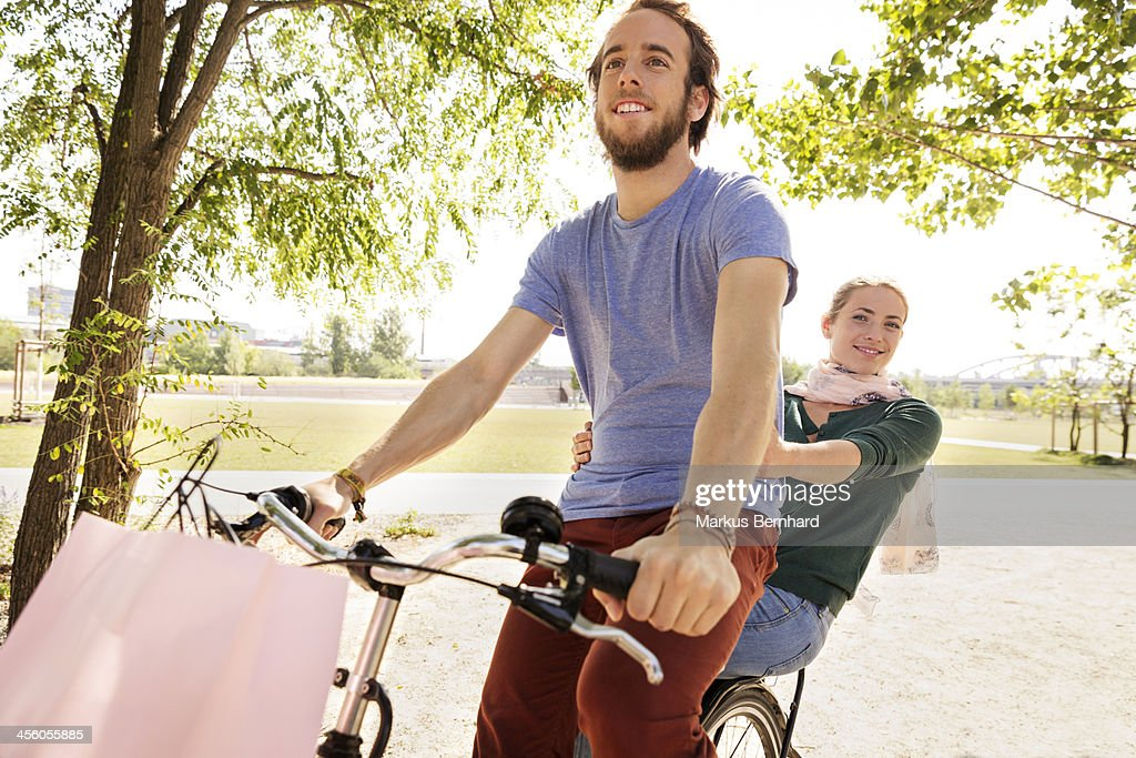 Couple share a ride on their bicycle. : Stock Photo