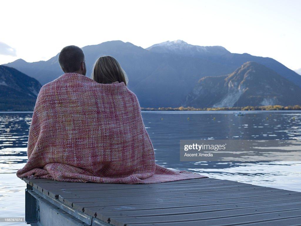 Couple share blanket before sunrise, on lake pier