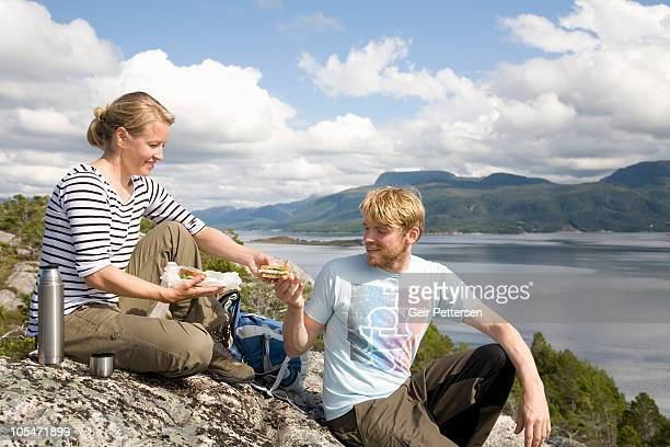 Couple share packed lunch on rock above fjord